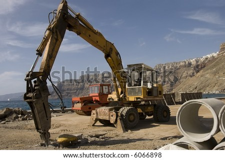 drill in motion digging hole on a construction site on the pier of Fira, Greece