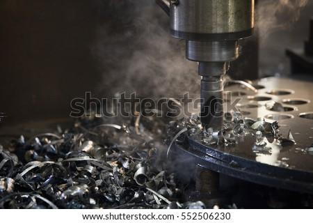 Drill press drilling a steel plate