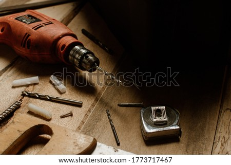 drill with metal bits accompanied by a meter and a bolt. DIY and carpentry work concept.