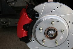Drilled and Slotted Brake Rotor with Red Caliper on a five bolt hub. Jack in the background holding the car.