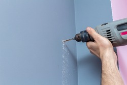 Drilling a gray wall with a drill close-up