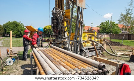 Drilling Geothermal Well.  Workers on Drilling Rig. A worker prepares to join two pieces of drill pipe on a drilling rig. Drilling geothermal well for a residential geothermal heat pump.