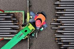 Drilling machine loading with drilling pipes by operator