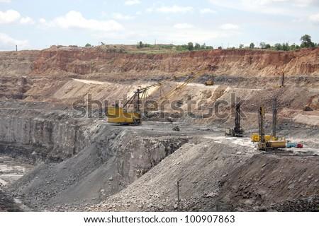 Drilling machines & dragline excavator in a open cast mine - stock photo