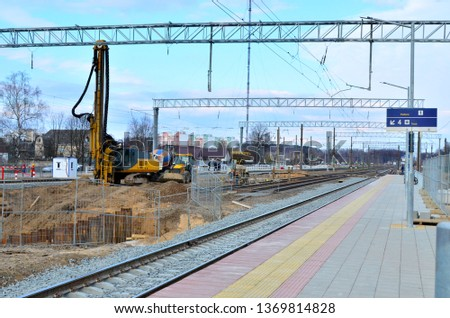 Drilling piling machine for driving piles into the ground in the pit. Construction site with heavy equipment on railroad during the construction of railway station and underground pedestrian crossing