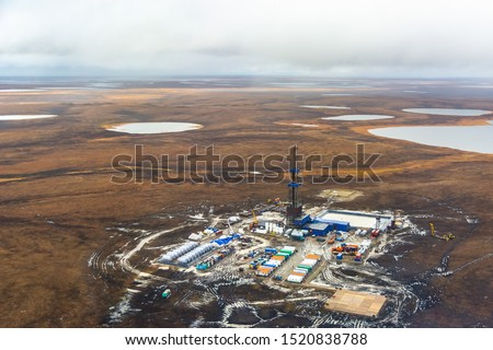 Drilling rig and equipment at an oil field in the northern tundra. Top view from a helicopter. Autumn tundra with lakes beyond the Arctic Circle.