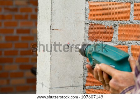 Drilling the wall with electric drill