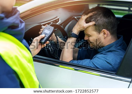 drink and drive concept - sad drunk man sitting in the car after police alcohol test with alcometer Foto stock ©
