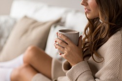 drink, christmas and hygge concept - close up of happy woman with cup of coffee in bed at home
