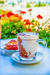 Drink in a large glass cup - Hot Chocolate: Chocolate, hot frothed milk, cocoa. in a summer city cafe or restaurant stands on the table, next to a puff pastry