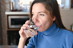 Drink plenty of water from the virus, Covid-19 Pandemic Coronavirus. Girl drinks water from a glass