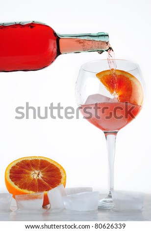 drink poured into the cup with ice and slice of orange