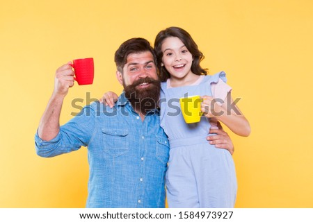 Drink water. Drink fresh juice. Breakfast concept. Good morning. Having coffee together. Healthy lifestyle. Family drinking tea. Bearded man and happy girl holding mugs. Father and daughter hot drink.