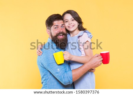 Drink water. Drink fresh juice. Breakfast concept. Good morning. Having coffee together. Lovely family tradition. Drinking tea. Bearded man and happy girl holding mugs. Father and daughter hot drink.