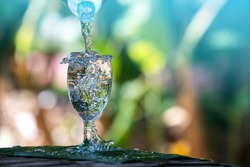 Drink water pouring in to glass over sunlight and natural green background.Select focus blurred background.Photo select focus.