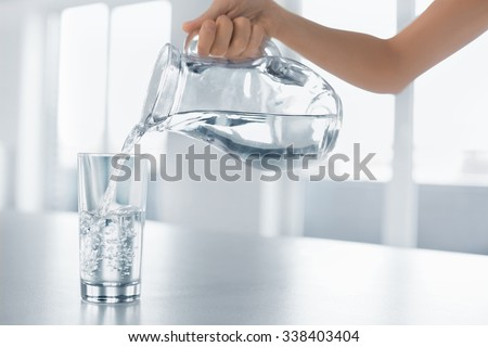 Drink Water. Woman's Hand Pouring Fresh Pure Water From Pitcher Into A Glass. Health And Diet Concept. Healthy Lifestyle. Healthcare And Beauty. Hydratation. #338403404