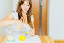 Drink water. Woman's hand pouring fresh pure water with pieces of lemon from pitcher into glass in the morning Health and diet concept. Healthy lifestyle. Health care and beauty. Hydration.