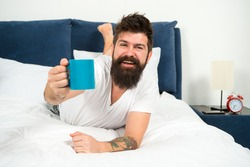 Drink with relish. Happy hipster offer hot cup. Pleasure of coffee. Bearded man give cup of coffee. Enjoying cup of pleasure. Pleasure and joy. Pure pleasure. Enjoy yourself. Good morning.