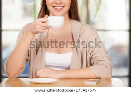 Drinking a fresh coffee. Cropped image of beautiful young woman drinking coffee at the restaurant and smiling at camera