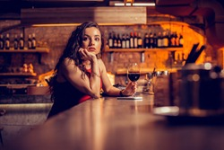 Drinking and waiting. Long-haired curly woman drinking wine and waiting for her man in the bar