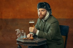 Drinking beer. Portrait of red headed and bearded man playing famous artist Van Gogh isolated on dark orange bacground. Concept of art, eras comparison, fashion. imitation, humor, ad. Bandaged ear.
