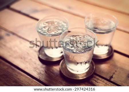 Drinking cold water into a  three glass placed on the wooden table.