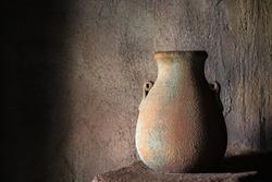 Drinking earthenware jug on stone shelf indoors