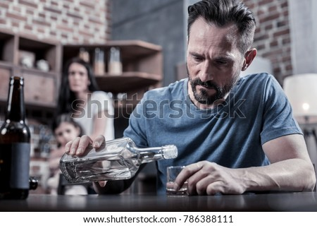 Drinking father. Serious unhappy sad man sitting at the table and pouring vodka into his glass while having alcohol addiction