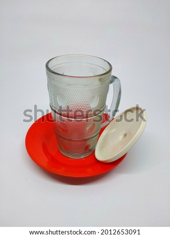 Drinking glasses and saucers. Transparent drinking glass on a saucer. This photo of drinking glasses and saucers is taken from the side. The background of the photo of drinking glasses and saucers is  Stock photo ©