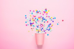 Drinking Paper Cup with Multicolored Confetti Scattered on Fuchsia Background. Flat Lay Composition. Birthday Party Celebration Kids Fun Cheerful Atmosphere. Greeting Card Poster Template. Copy Space