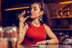 Drinking red wine. Beautiful woman wearing nice earrings drinking red wine while sitting alone in bar
