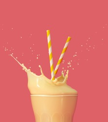 drinking straws into a splashing glass of yellow milkshake on pastel pink background