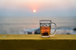 Drinking tea in a beer mug by the sea at sunset by the beach