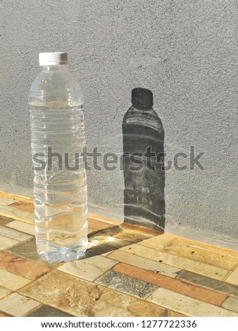 Drinking water bottles are located beside the gray walls. #1277722336