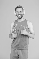 Drinking water. Cheerful athletic guy listening music. Keep body and mind in good shape. Happy sportsman hold water bottle. Fitness trainer. Feeling thirst. Thirst and dehydration. Thirst control