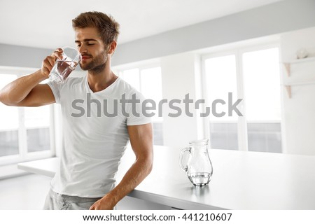 Drinking Water. Closeup Portrait Of Handsome Young Man With Sexy Fit Body Drinking Fresh Water From Glass In Morning. Thirsty Fitness Male Model Enjoying Refreshing Drink Indoors. Healthy Nutrition
