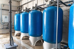 Drinking water factory or plant production, industrial interior. Large metal tanks for filtering and potable water treatment from well.