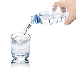 Drinking water is poured from a bottle into a glass