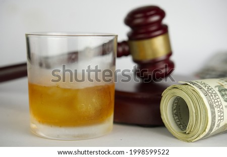 Drinking with driving offenses.Close up of glass of whisky with gavel hammer background. Foto stock ©