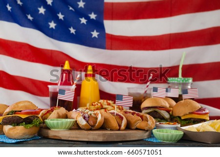 Drinks and snacks arranged on wooden table against American flag