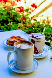 Drinks in a summer city cafe or restaurant are on the table: a large white mug with coffee and hot chocolate in a large glass cup (Chocolate, hot frothed milk, cocoa), next to a puff pastry