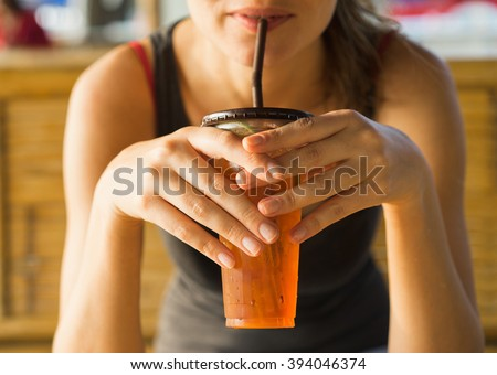 drinks, people and lifestyle concept - close up of  woman drinking ice tea  from plastic cup with straw at cafe