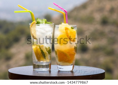 Drinks Refreshing. Bright summer refreshments made from juicy fruits. Two glasses of citrus fruits with ice and mint on the background of the hill #1434779867