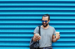 drinks, technology and people concept - close up of man with coffee cup and smartphone on street over ribbed blue wall background