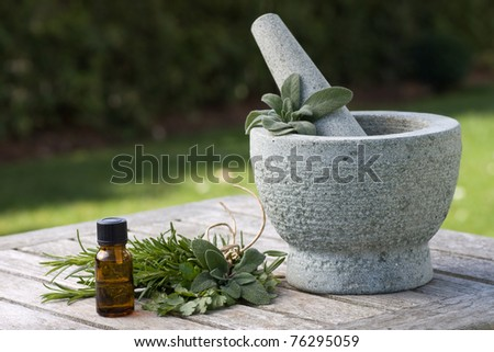 Drip bottle, pestle and mortar, with fresh foliage in the background - stock photo