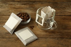 Drip coffee bags, beans and glass cup on wooden  table