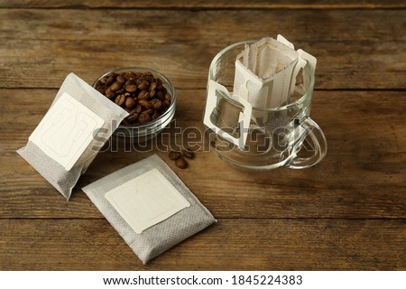 Photo of  Drip coffee bags, beans and glass cup on wooden  table