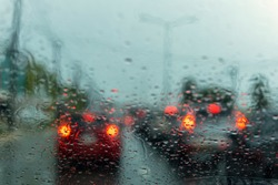 drive a car on the road stop witn trafic light with raindrop over the wind shield. Shot form wind shield