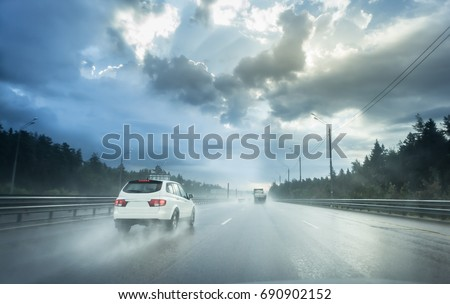 Drive car in rain on asphalt wet road. Clouds and sun.