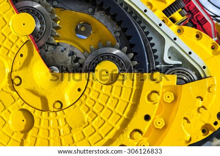 Drive gear and bearings, cross section of bulldozer sprocket internal mechanism, large construction machine with bolts and yellow paint coating, heavy industry, detail